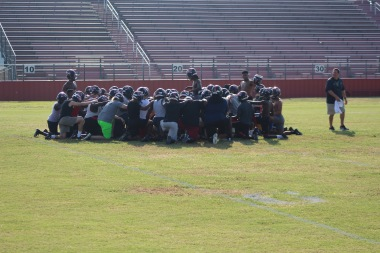 Football players prior to the event huddling and praying together.